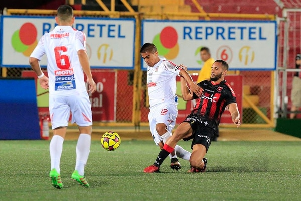 Josué Rodríguez (Belén) intenta seguir con el balón ante la barrida del jugador de Alajuelense Iago Soares.