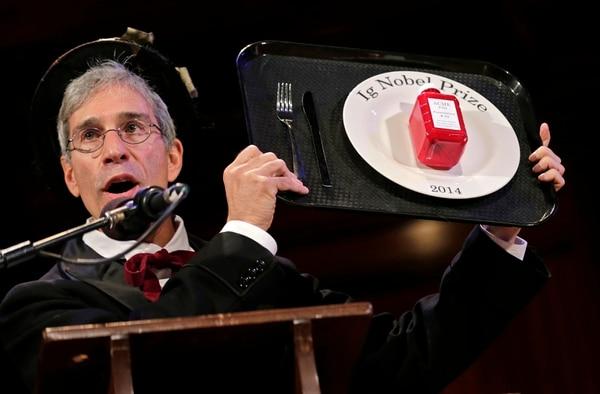 El maestro de ceremonias Marc Abrahams sostiene el trofeo del Premio Ig Nobel 2014 durante la ceremonia en la Universidad de Harvard, en Cambridge, Massachusetts. Estos reconocimientos son entregados por la revista Annals of Improbable Research y destacan descubrimientos científicos 'tontos' que a menudo tienen aplicaciones sorprendentemente prácticas. (AP / Charles Krupa)