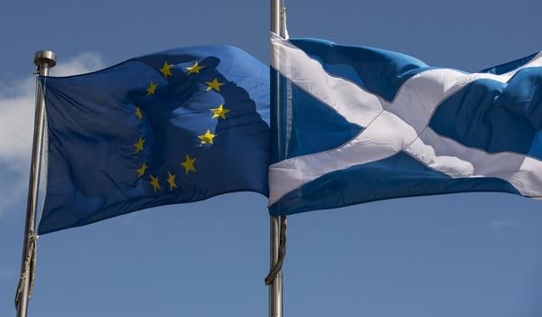 Banderas de Escocia (cerecha) y de la Unión Europea flameaban en el edificio del Parlamento local en Edimburgo.