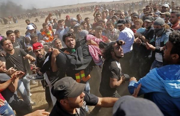 Palestinos cargan a un manifestante herido en las protestas en la frontera entre la Franja de Gaza e Israel. Foto AFP: Thomas Coex
