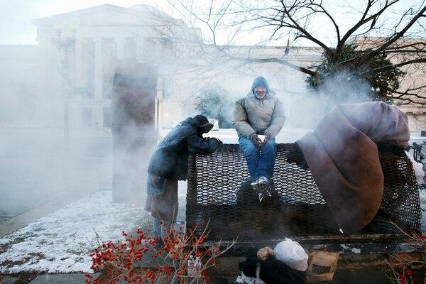 Personas sin techo luchaban ayer contra el intenso frío en Washington valiéndose de un calentador de vapor. Ellos se encontraban a pocas cuadras del Capitolio. | AP.