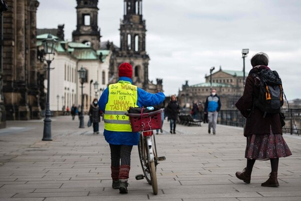 Una mujer vestida con un chaleco con la inscripción 'La dignidad del ser humano es inviolable', en referencia al primer artículo de la Constitución alemana, camina por el centro de la ciudad de Dresde, en el este de Alemania, el 17 de abril del 2021. La administración de la ciudad prohibió una manifestación del movimiento 'Querdenker'. Foto: AFP