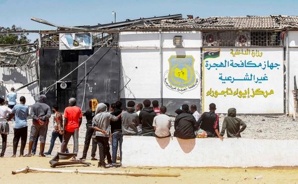 Decenas de migrantes esperan en las afueras de un centro de detención, en el suburbio de Tajura, en la capital, Tripoli, luego de un ataque aéreo en un edificio cercano que dejó decenas de muertos la noche anterior. Foto: AFP