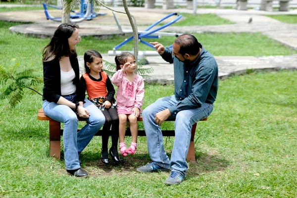 Lucie López le dijo en señas a su papá, Leonel, que estaba viendo volar un pajarito. En la foto aparecen su mamá Caroline y su hermana Sofía. Foto: Rafael Murillo