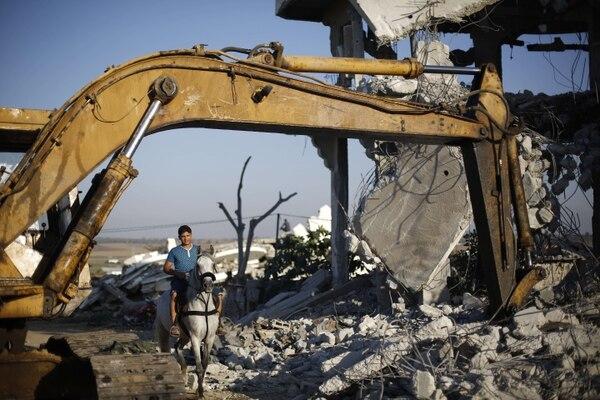 Un palestino monta su caballo a través de los escombros de edificios en Gaza.