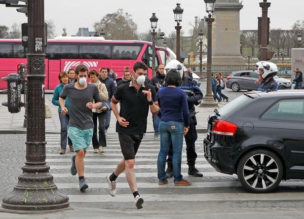 Dos personas pasan corriendo por la Plaza Concordia, en París, usando máscaras protectoras, mientras un policía controla el tráfico de vehículos.