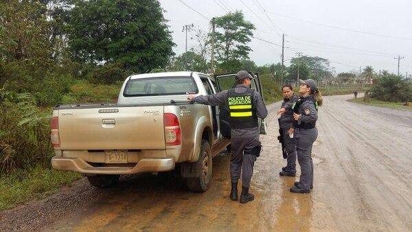 Oficiales de la Policía de Migración dialogaban la mañana de este sábado en el sector de Coopevega, distrito de Cutris, San Carlos, donde anoche se registró un muerto por un enfrentamiento. Foto: Carlos Hernández.