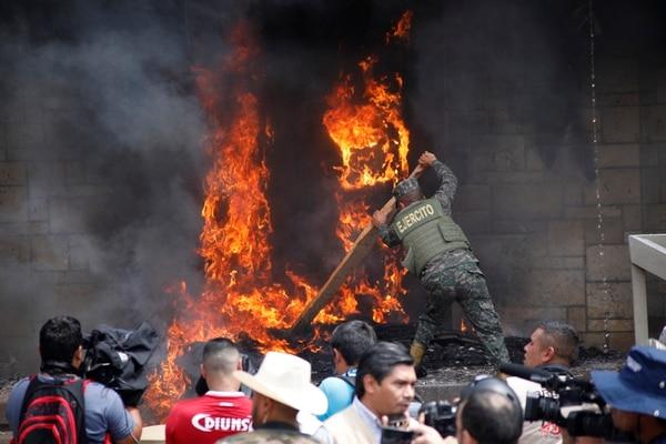 Un soldado trataba de retirar una llanta encendida que lanzaron presuntos manifestantes en la entrada de la embajada estadounidense en Tegucigalpa, este viernes 31 de mayo del 2019.