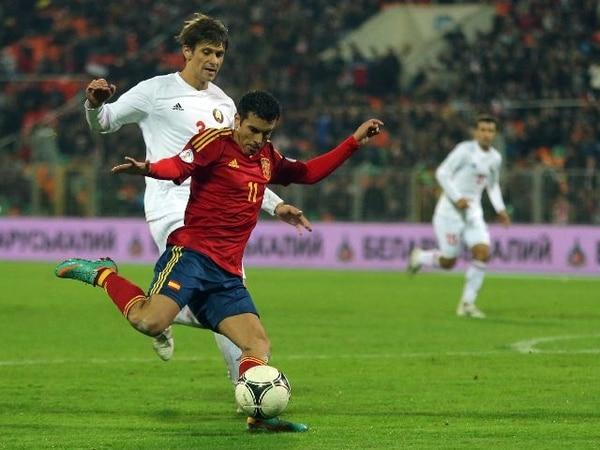 El español Pedro Rodríguez perfila su disparo ante la marca del bielorruso Aleksandr Martynovich. El delantero anotó un triplete ayer. | AP