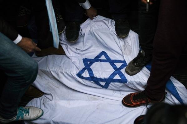 Manifestantes egipcios pisan una bandera israelí durante una protesta en El Cairo contra el reconocimiento de Estados Unidos a Jerusalén como capital de Israel, el 7 de diciembre de 2017.