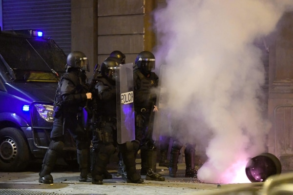 Una bomba de humo lanzada por manifestantes cae cerca de miembros de la Policía regional catalana Mossos d'Esquadra tras una manifestación contra el encarcelamiento del rapero español Pablo Hasel en Barcelona el 21 de febrero del 2021. Foto: AFP