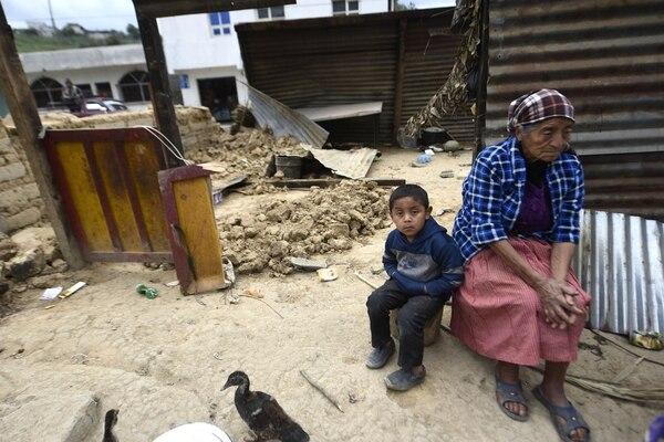 Dos residentes afectados entre los escombros en Tacaná, Guatemala.