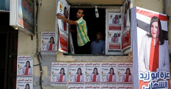 Un voluntario cuelga un afiche de Azzah Abu Zeid al Shahabi, una candidata parlamentaria independiente en la sede de la campaña en Alejandría Egipto, el sábado 17 de octubre.