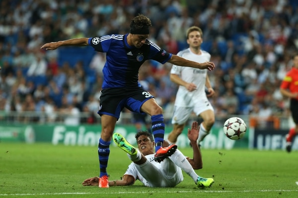 Cristian Bolaños (azul), futbolista costarricense del Copenhague danés, marca a Raphael Varane, francés del Real Madrid durante el partido de este miércoles en el estadio Santiago Bernabéu.