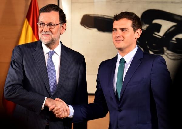 El presidente interno del gobierno español, Mariano Rajoy, estrecha la mano del líder del centrista partido Ciudadanos Albert Rivera (der.).