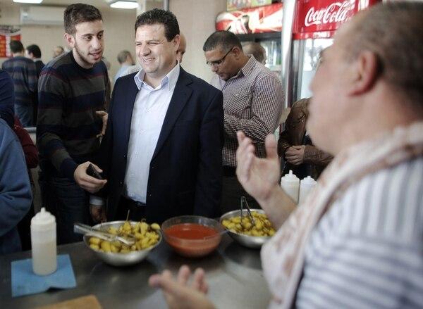 Ayman Odeh (centro), líder de la lista unida de partidos árabes israelíes, visitó ayer un quiosco de comidas rápidas en la vieja ciudad de Acre en la recta final de la campaña electoral. | AFP