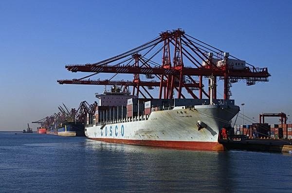 Un barco recibe carga en el puerto de Rizhao, al este de China. La caída en las exportaciones del país estrechó su superávit comercial. | AFP