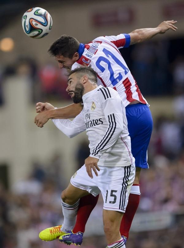 Cristian Rodríguez, del Atlético de Madrid, le gana el balón al defensor merengue Daniel Carvajal dureante el juego de ayer por la Supercopa. | AFP