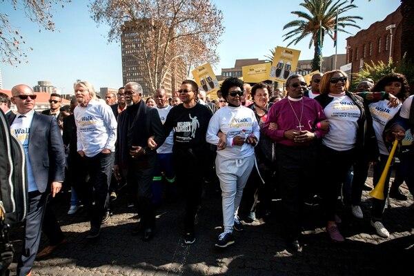 La viuda de Nelson Mandela, Graca Michel (vestida de blanco), encabeza junto a otras personalidades mundiales la marcha para conmemorar el centenario del nacimiento de Mandela en Johannesburgo el 18 de julio de 2018. AFP