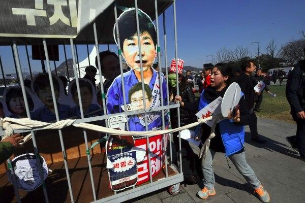 Activistas antigubernamentales cargan una prisión simulada para pedir la detención de la presidenta de Corea del Sur Park Geun-Hye, después del anuncio de la Corte Constitucional de destituir a la mandataria.