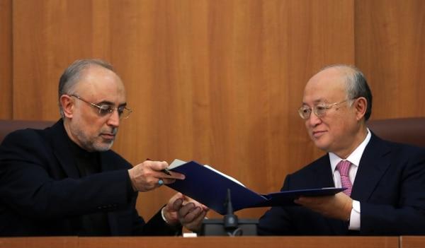 Ali Akbar Salehi (izquierda) líder de energía atómica de Irán y el director del Organismo Internacional de Energía Atómica,Yukiya Amano, firman el protocolo.