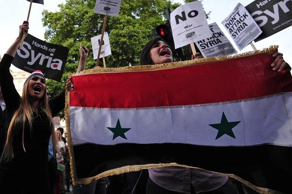Una mujer sostiene una bandera de Siria para oponerse a una posible intervención extranjera durante una manifestación en Londres. Escenas así se repitieron en otros países de Europa. | AFP: