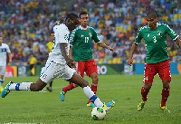 El italiano Mario Balotelli se filtra entre los defensas mexicanos Carlos Salcido (3) y Jesús Zavala durante el partido del domingo. / AFP