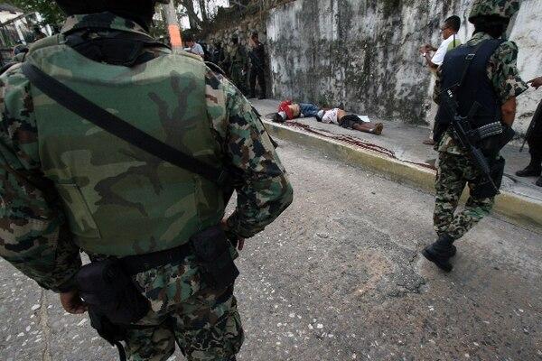 Soldados mexicanos custodiaban el lugar donde yacían dos hombres asesinados, cerca de la avenida Costera, en Acapulco.