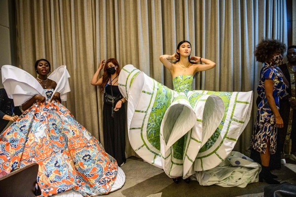 This picture taken on November 6, 2020 shows Harmony Anne-Marie Ilunga (L), 22, who moved to Hong Kong as a child refugee from the Democratic Republic of Congo, and other models getting ready in the backstage area before the 'Harmony IV' fashion show in Hong Kong, which aims to celebrate the city's diversity. - As a young black woman modelling in Hong Kong, Harmony Anne-Marie Ilunga rarely saw anyone who looked like her in the magazines. Now the 22-year-old is trying to change that -- one model at a time. (Photo by Anthony WALLACE / AFP)