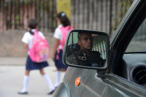 Miembro de la Policía Militar vigila la llegada de estudiantes a la escuela Maximiliano Sagastume, en Tegucigalpa, el 17 de marzo del 2017. Foto: AFP