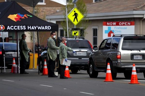 Bomberos ayudaban agente que esperaba turno para realizarse una prueba de covid-19 en Hayward, California, este martes 24 de marzo del 2020.