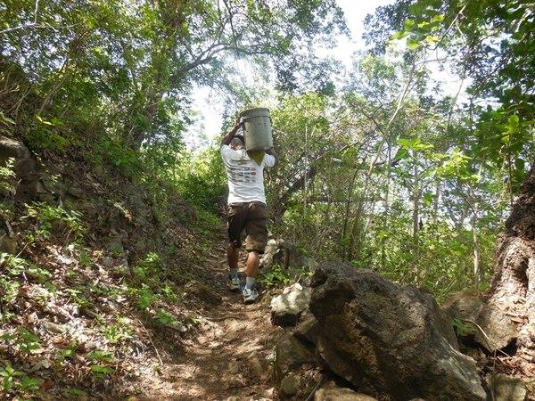 Un vecino de Altos del Roble camina por un sendero de montaña, luego de recolectar el agua en uno de sus baldes. | REBECA ÁLVAREZ