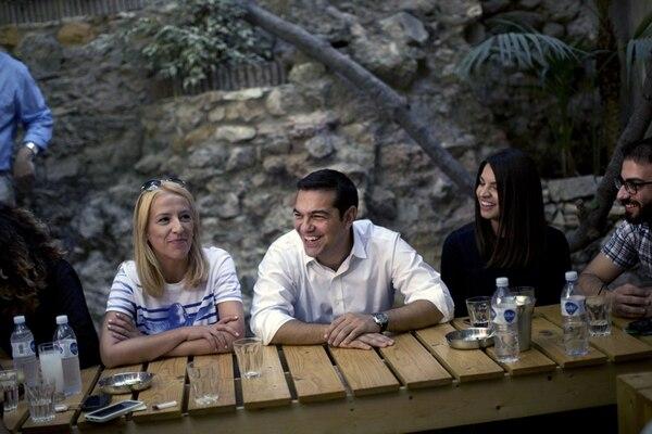 El exprimer ministro griego Alexis Tsipras y líder del izquierdista Syriza partido (centro), se reunió este sábado con jóvenes en un café en el centro de Atenas antes de las elecciones legislativas griegas.   AFP