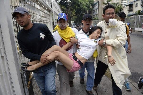 Mujer recibe atención durante protestas en contra de Maduro, 1 de mayo de 2017