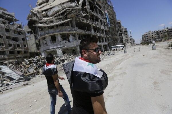 Hombres sirios caminan cerca de los edificios destruidos en el barrio de Homs Khaldiyeh, anteriormente en manos de los combatientes rebeldes y capturado por las fuerzas del gobierno sirio.