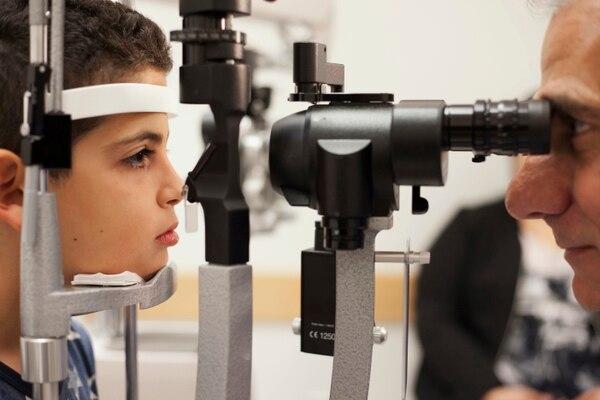 En esta foto de archivo del 4 de octubre de 2017, el doctor Albert Maguire, a la derecha, revisa los ojos de Misa Kaabali, de 8 años, en el Hospital de Niños de Filadelfia. Misa tenía 4 años cuando recibió su tratamiento de terapia genética. (AP Photo/Bill West)