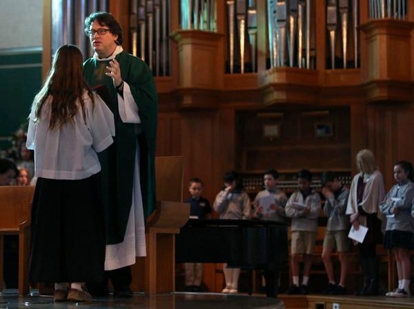 Natalie Kricken, estudiante de la Escuela Catpolica Santa Rita, ayuda al sacerdote Josh Whitfield durante la misa semanal que oficia en ese centro educativo en Dallas, Texas.