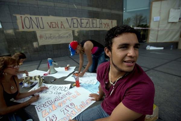 Estudiantes hacen carteles en las afueras de la oficina de Naciones Unidas en Caracas, donde han acampado para pedir al organismo internacional que vaya a Venezuela a observar la situación política y social. | AP