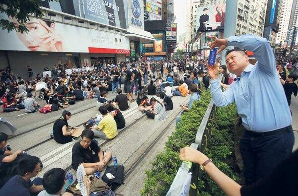 Un visitante toma una foto de una protesta sentada en Hong Kong. Manifestantes pro-democracia ampliaron sus mítines en todo Hong Kong.