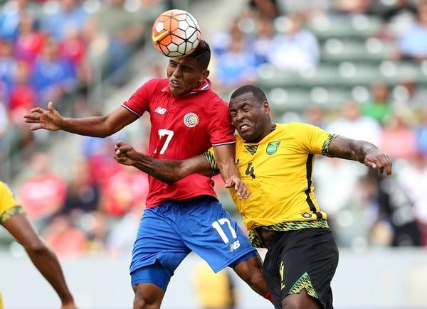 Johan Venegas lucha por el balón con el defensor jamaiquino Westley Morgan.   AFP