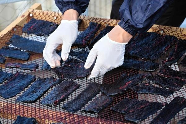 Un rabajador de la compañía ballenera japonesa Gaibo Hogei pone bajo el sol rodajas de carne de ballena cruda. (Kazuhiro NOGI / AFP)