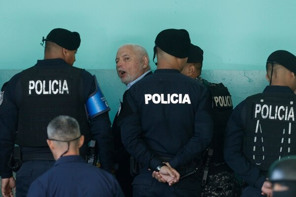 Former Panamanian President Ricardo Martinelli, center, is escorted by police as he arrive to a court hearing in Panama City, Friday, March 22, 2019. Martinelli, who was president from 2009 to 2014, is accused of embezzlement and illegally monitoring phone calls and other communications. Last week after a team of psychiatrists doctors declared him able to stand trial they warned that he should continue his trial. (AP Photo/Arnulfo Franco)