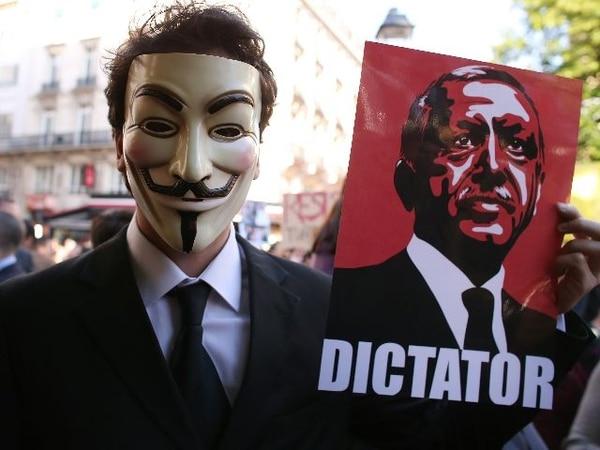 Un hombre con una máscara utilizada por el personaje principal de la película 'V for Vendetta' sostenía hoy un cartel que califica al primer ministro turco de 'Dictador'. La manifestación se dio en protesta por los heridos durante manifestaciones y por la brutalidad policial de los últimos días. | AFP