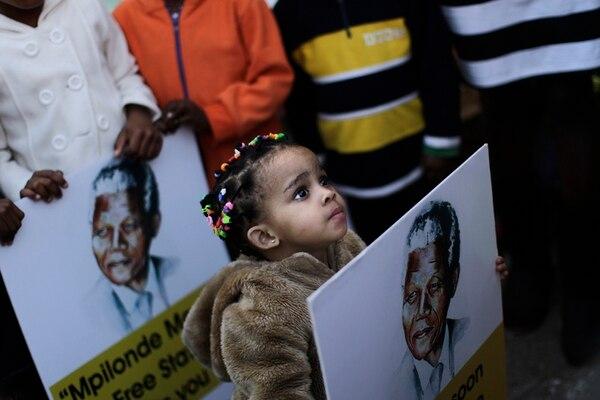 Una niña sostuvo el viernes un afiche de Nelson Mandela durante una vigilia realizada en Pretoria. | AP.