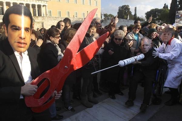 Manifestantes con máscaras de Alexis Tsipras, el primer ministro griego, y autoridades alemanas se reunieron en las afueras del Parlamento en Atenas para mostrar su apoyo a las políticas del Gobierno heleno.   EFE