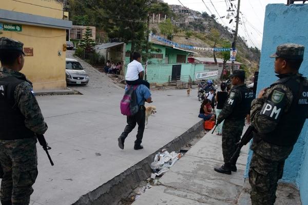 Efectivos de la Policía Militar vigilaban el viernes mientras un padre recogía a su hijo a la salida de la Escuela Maximiliano Sagastume en Sagastume, un barrio en el norte de Tegucigalpa.