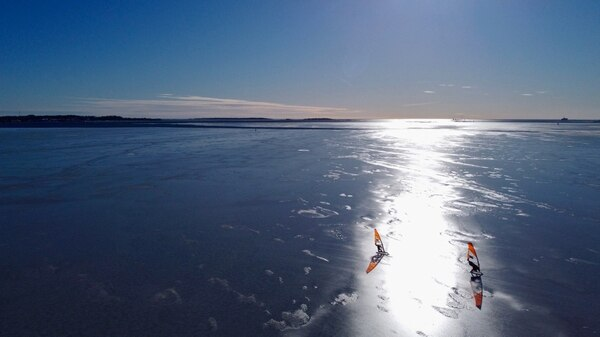 An aerial photo taken on February 28, 2021 shows ice surfers skating across the frozen Baltic Sea off the coast of Helsinki. - What to do if you are a windsurfing enthusiast in a country where the sea freezes over for months of the year? For a group of Finns, the answer is to kit out sailboards with skates and take to the ice, reaching speeds of up to 100km/h (62mph) in a burgeoning sport that can only be practised in a handful of places around the world. (Photo by Sam KINGSLEY / AFP) / TO GO WITH AFP STORY