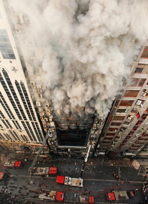 Los bomberos en plena lucha por sofocar el incendio que se desató este jueves 28 de marzo del 2019 en un edificio de oficinas en Daca, Bangladés.