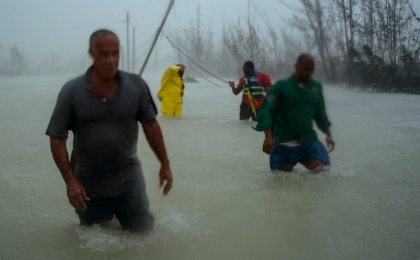 Voluntarios se desplazan a través de una calle completamente inundada mientras luchaban por rescatar gente cerca de Freeport, Gran Bahama, este martes 3 de setiembre del 2019.