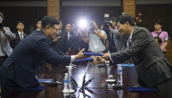 Suh Ho (izq.), de la delegación surcoreana, intercambia los documentos del acuerdo con su similar de Corea del Norte, Park Chol-su. | EFE.